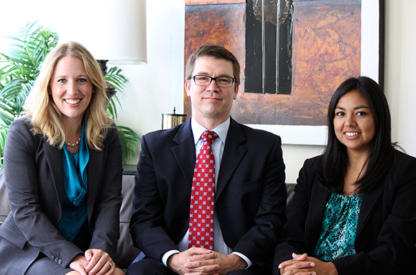 Photo showing three smiling team members representing the diversity at Perez & Morris