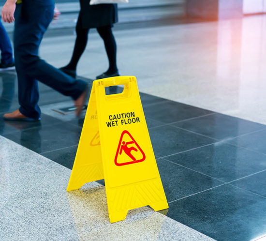 Photo of slippery floor with a caution sign and people walking near it